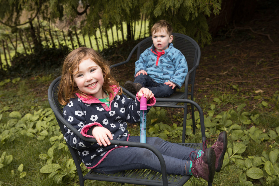 Brother and sister sitting on chairs