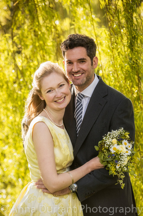 Bride and groom portrait back lit by the sun, in front of a willow tree