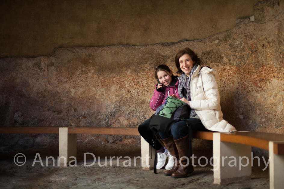 Mother and child sitting in alcove in The Roman Baths in Bath
