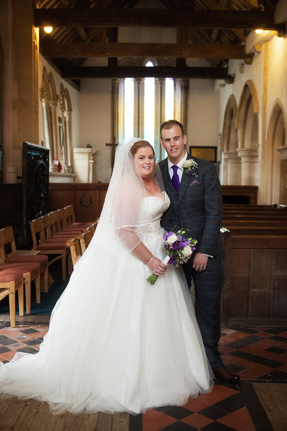 Bride and groom full length formal pose in church