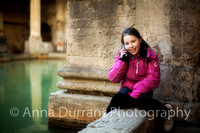 girl sitting by side of The Roman Baths in Bath