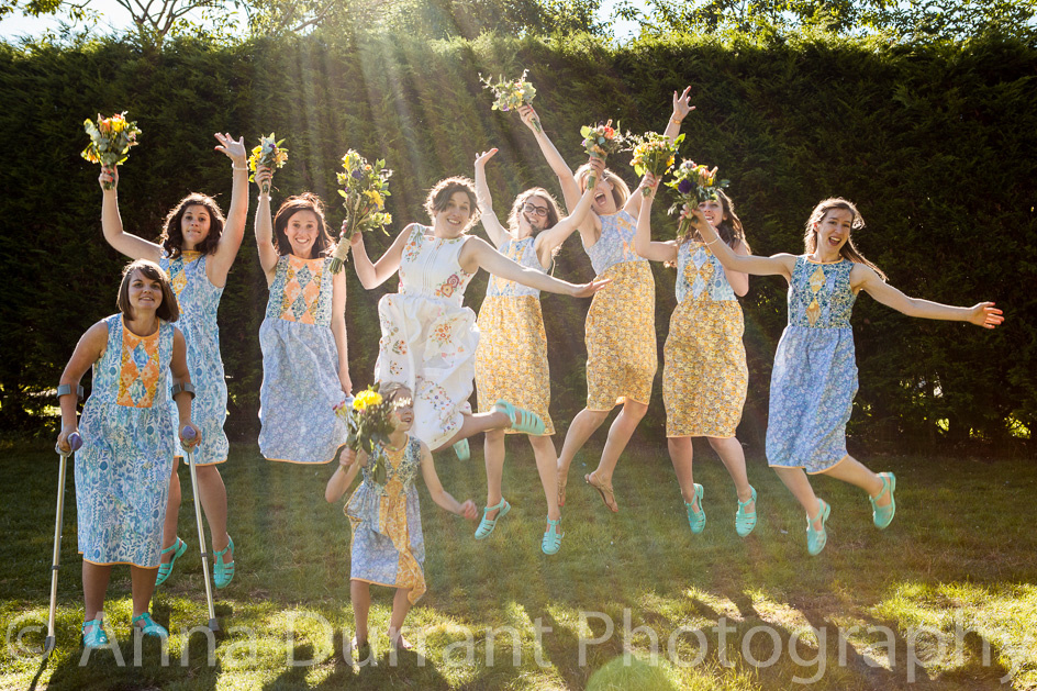 Bride and her bridesmaids jumping with sun streaming behind them.