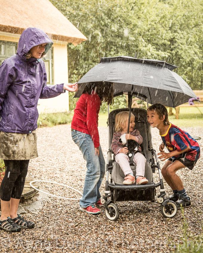 Children hiding under umbrella in rain storm