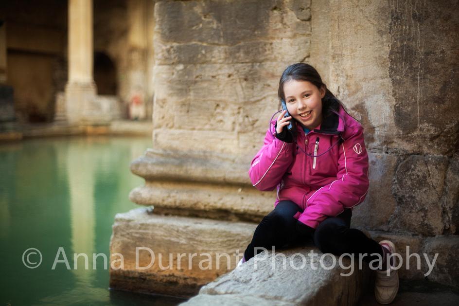 girl sitting by side of The Roman Baths in Bath