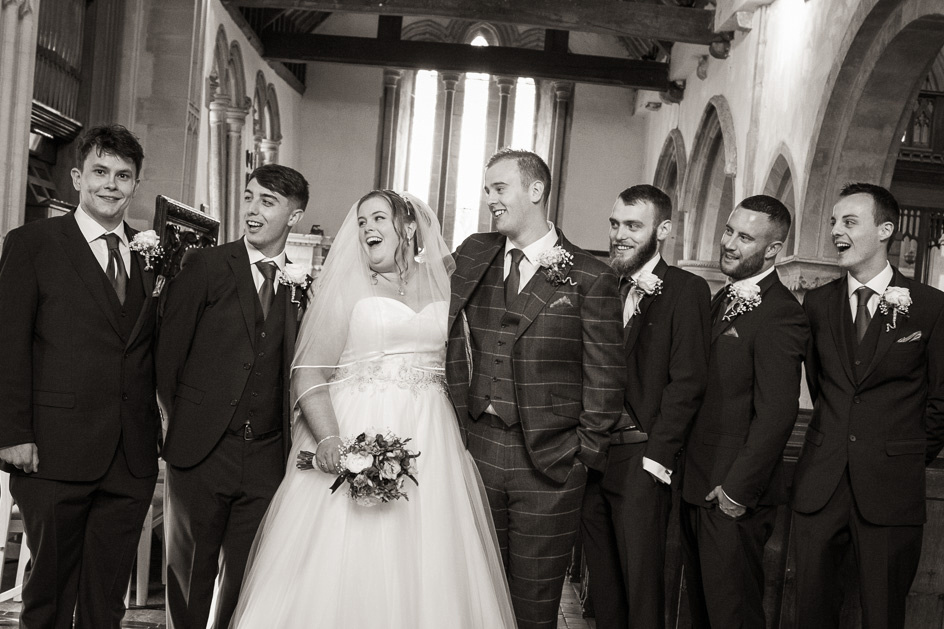 Black and white fun picture of ushers with bride and groom