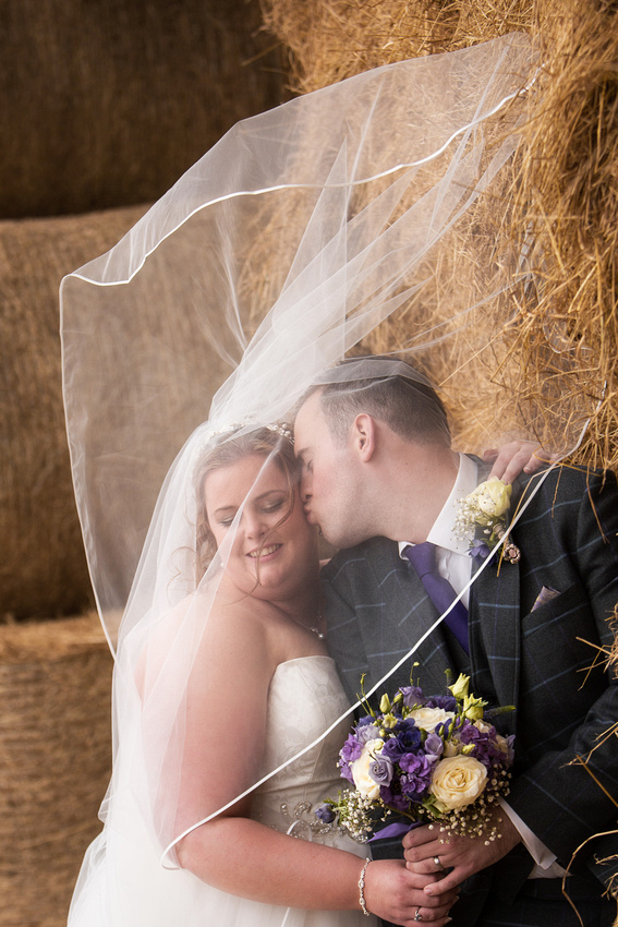 Wind blowing veil over bride and groom