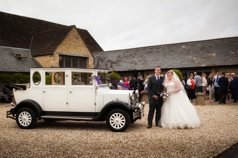 Couple by bridal car outside Winkworth Farm